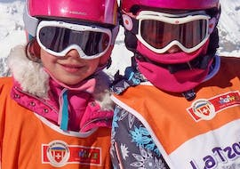 """Two little kids are smiling at the camera before starting their Kids Ski Lessons """"Snowgarden"""" (3-6 years) - Morning with the Swiss Ski School La Tzoumaz."""