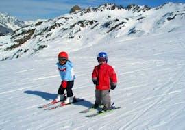 """Zwei Kinder haben Spaß mit ihrem Skilehrer der Skischule Klostertal während dem Kinder-Skikurs """"Schneemannland"""" (3-5J.) für Anfänger."""