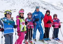 Young skiers are looking happy with their ski instructor from the ski school Prosneige Les Menuires while posing for a picture during their Kids Ski Lessons + Ski Pass (5-13 years).