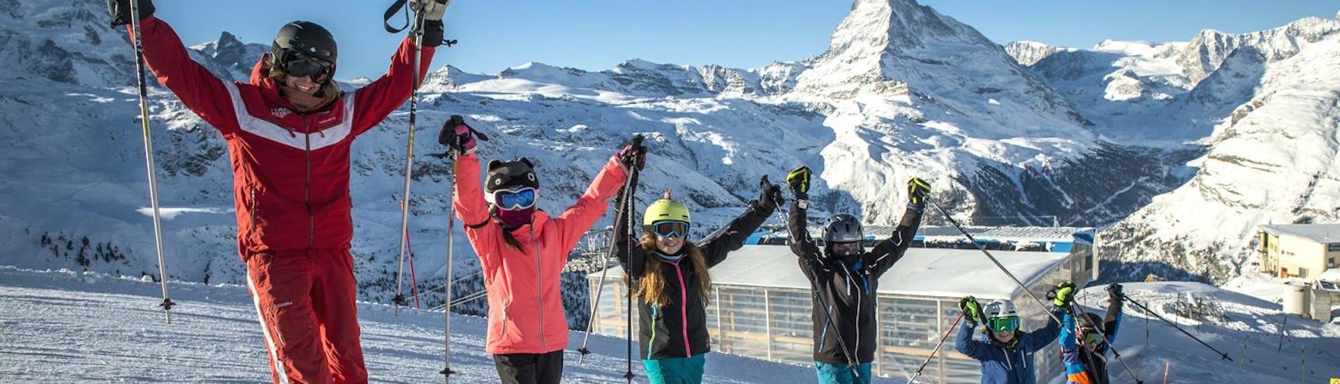 A group of young skiers and their ski instructor are posing for a group photo in front of the Matterhorn during their Kids Ski Lessons (6-14 years) - Beginners with Zermatters.