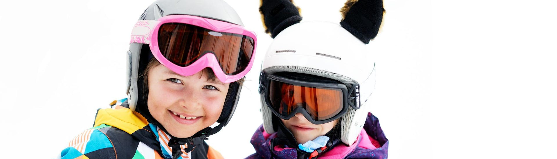 Two young children smiling at the camera during one of the Kids Ski Lessons (3.5-10 y.) for Beginners organised by TOP SECRET Ski- & Snowboard School Davos.