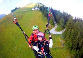 During the kids tandem paragliding in Stubaital the experienced tandem pilot of Fly-Stubai flies with a girl over a lush green meadow.