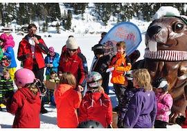 Kinder stehen im Kreis um Skilehrer