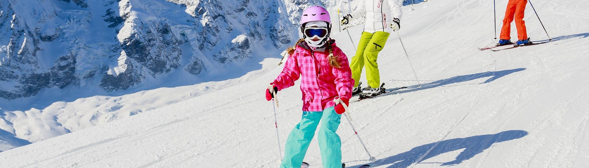 skiing kids with mountains at the background