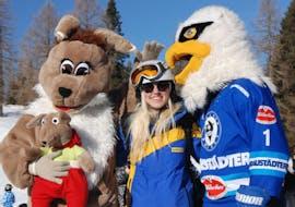 Skilehrerin mit Maskottchen beim Schikurs für Kinder (4-14 Jahre) - Fortgeschritten
