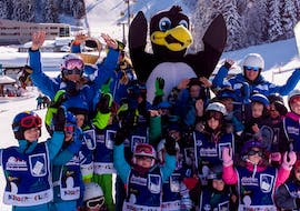 "A large group of children wave to the camera together with their ski instructor during the kids ski lessons ""BOBOs Miniclub"" (3-4 years) - beginner of the Ski School Fieberbrunn Widmann Mountain Sports."