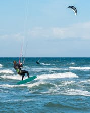 A young man sliding on the wave in Fehmarn while windsurfing.