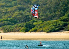 A kitesurfer is practicing his technique under perfect conditions during the Kitesurfing Lessons at Lagoa de Albufeira in Sesimbra with Meira Pro Center Sesimbra.