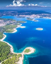 A panoramic view of a city on the cliffside in Croatia where you can do windsurfing and kitesurfing in Pula.