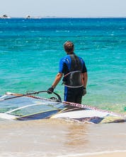 A young man is stood knee-deep in the sea with his board and sail, ready to go windsurfing in Naxos.