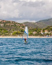 Un uomo dall'aspetto sportivo è raffigurato mentre fa windsurf vicino a Porto Pollo.