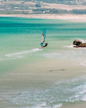 A man who is windsurfing in Tarifa can be seen riding the waves of the Strait of Gibraltar.