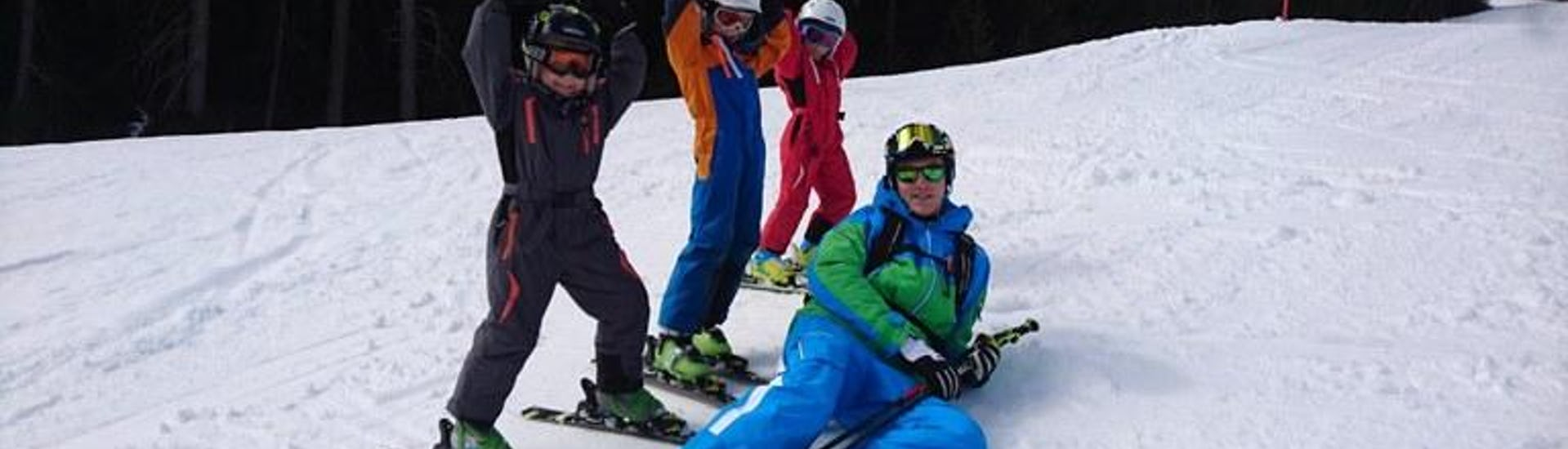 Kids lie in the snow with private instructor