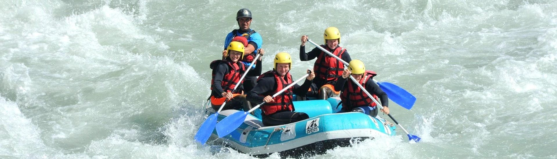 A group of friends is paddling on rapids during their rafting tour with Latitude Rafting.