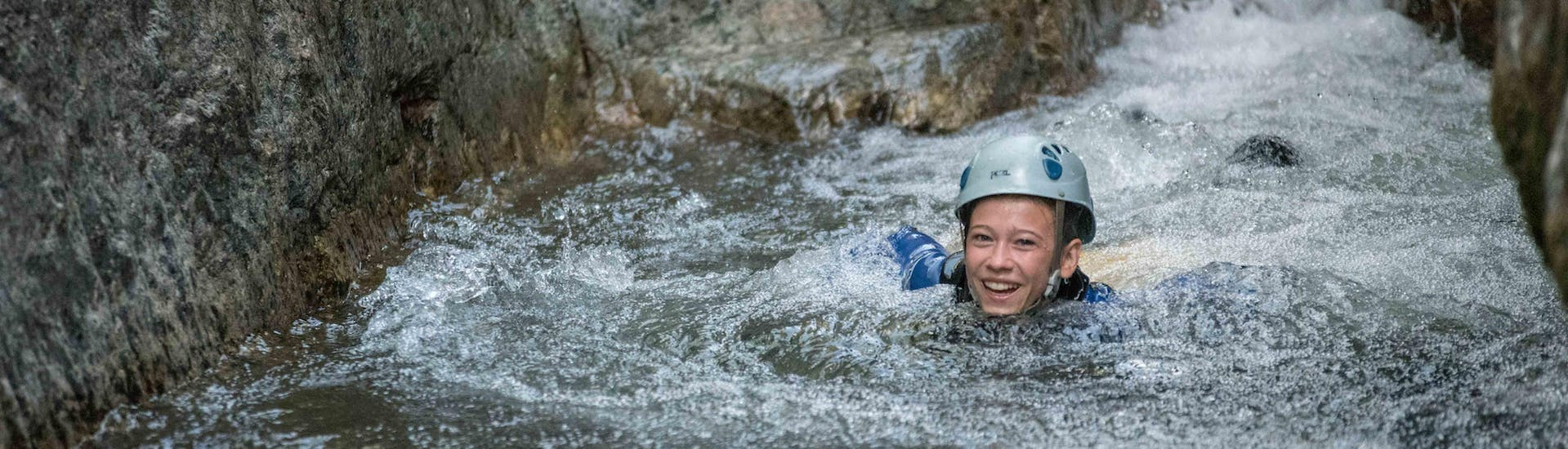 A canyoning enthusiast is swimming in a natural pool during a canyoning tour with Les Intraterrestres.