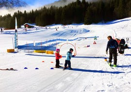 "Children practice skiing on the practice area during their Kids Ski Lessons ""SnowGarden"" (3-4 years) - Beginners with the ski school Diablerets Pure Trace."