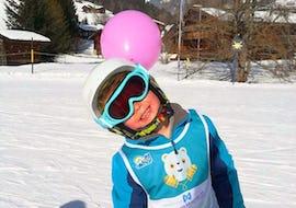 Kind lächelt in die Kamera während seinem Kinder Skikurs (5-16 Jahre) - Alle Levels mit der Skischule Diablerets Pure Trace.