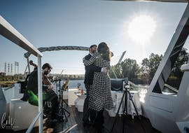 A couple dances relaxed on deck during their Boat trip on the Río Guadalquivir with 6-course menu organized by Fun Ride Sevilla.