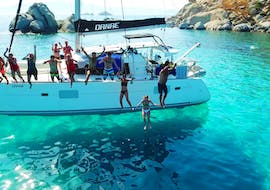 Friends are jumping into the crystal clear water during their Luxury Catamaran Cruise from Naxos with Snorkeling Breaks with Naxos Yachting.