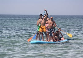 A whole family having fun with the Mega Stand Up Paddleboard rental in Armação de Pera with Moments Watersports Algarve.