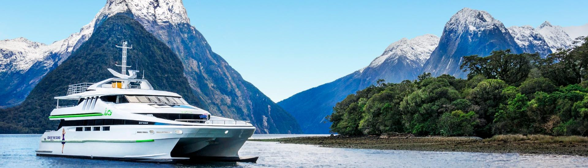 """A beautiful view on a luxurious catamaran from Jucy Cruise leaving for the Milford Sound Cruise """"Premium"""" - Winter."""