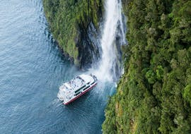 A catamaran operated by Southern Discoveries is approaching a waterfall during the Milford Sound Scenic Day Trip from Queenstown.