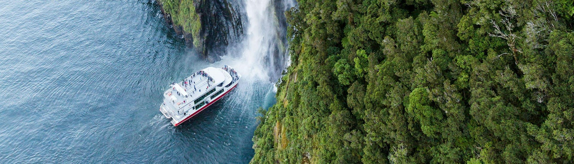 One of the catamarans operated by Southern Discoveries can be seen approaching a waterfall during the Milford Sound Scenic Day Trip from Queenstown - Winter.