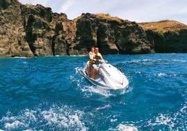 Two participants of the Mini Jet Ski Safari from Kamari Beach with Snorkeling organized by Kamari Beach Watersports Santorini are discovering the beautiful volcanic landscape of Santorini on a Jet Ski.