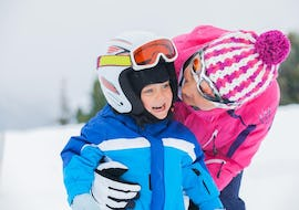 "Mother hugs her kid which is doing Ski Lessons ""All-in-One"" (3-5 years) - Beginner"
