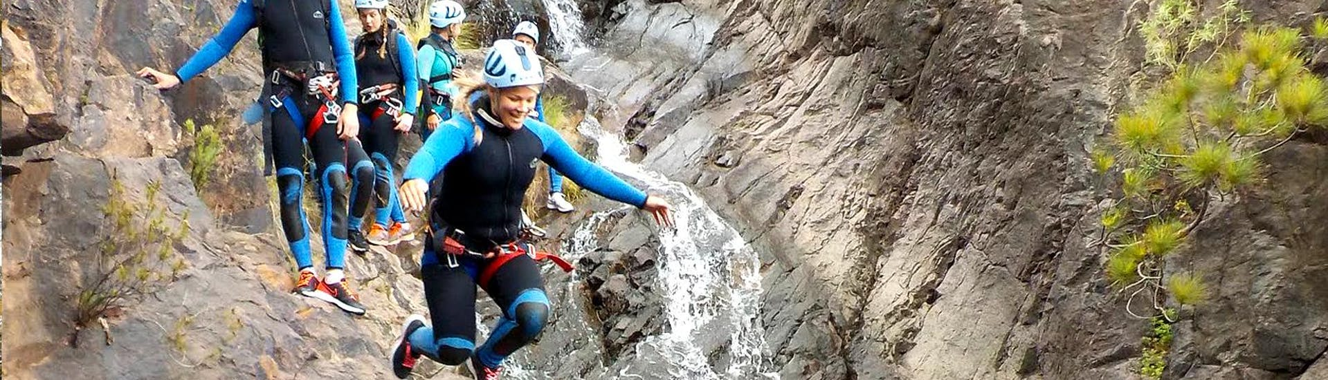 During the Canyoning at Barranco de la Manta in Gran Canaria a woman jumps from the cliff into the water under the supervision of the guide from Mojo Picón Aventura.