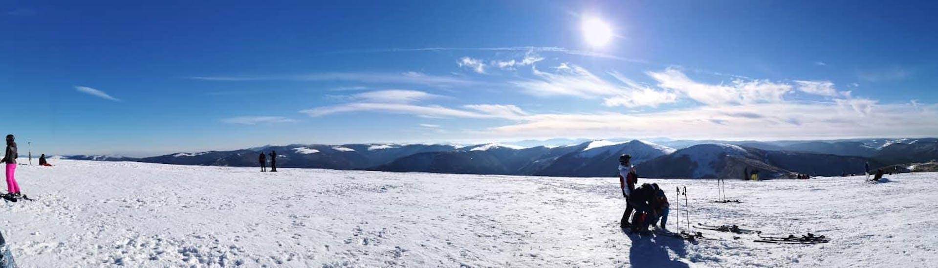 Eine Gruppe Skifahrer steht am Beginn der Skipiste und blicken über das Skigebiet La Bresse, wo die Skischule Moonshot Skikurse für all jene anbietet, die das Skifahren lernen wollen.