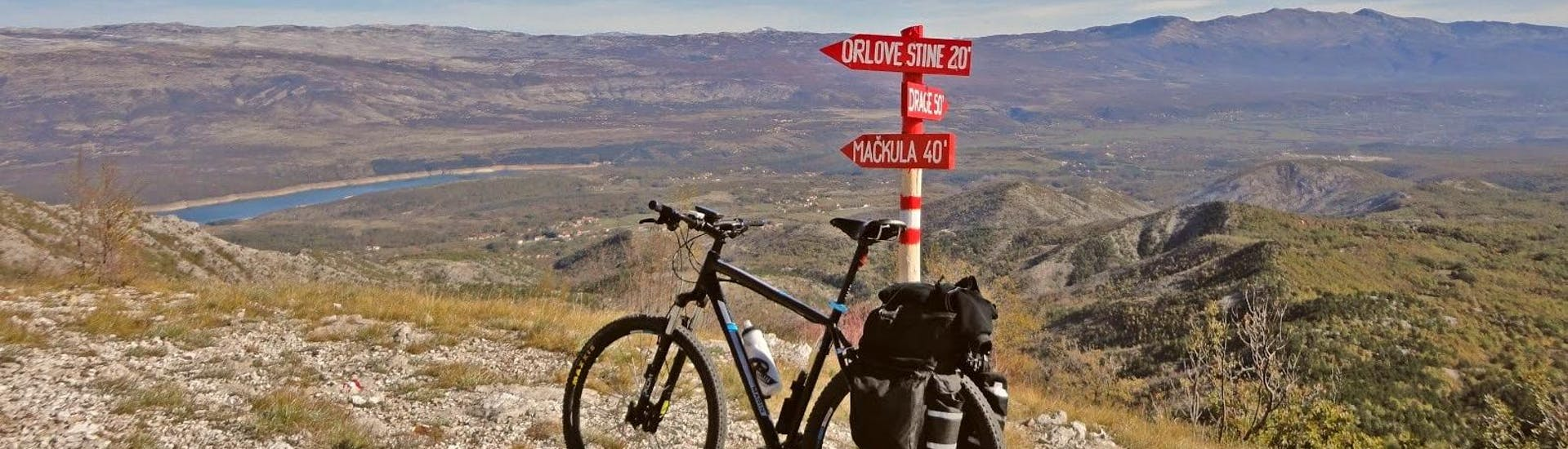 During the Extreme Svilaja Mountain Bike Tour from Sinj organise by Hotel Alkar, a cyclist is taking a picture of the beautiful Dalmatian landscape.