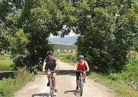 A couple is enjoying the Fun Bike Tour from Sinj with a certified guide from Hotel Alkar.