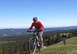 "A couple is doing the Mountain Bike Tour ""Jura Ridges"" - All Levels activity with La Boîte à montagne."