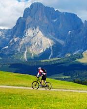 Un uomo, mentre va in mountain bike sull'Alpe di Siusi, percorre un prato verde ai piedi di un'alta catena montuosa.