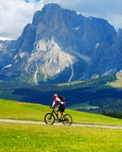 A man can be seen cycling along a green meadow at the foot of some rugged mountains while mountain biking at Seiser Alm.