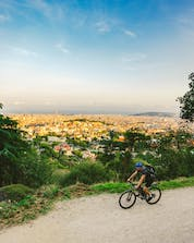 A man riding abbike with a view of a sunset in Barcelona where you can mountainbike.