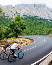 Zwei junge Männer unterwegs mit wunderschöner Aussicht beim Mountainbiken auf Mallorca.