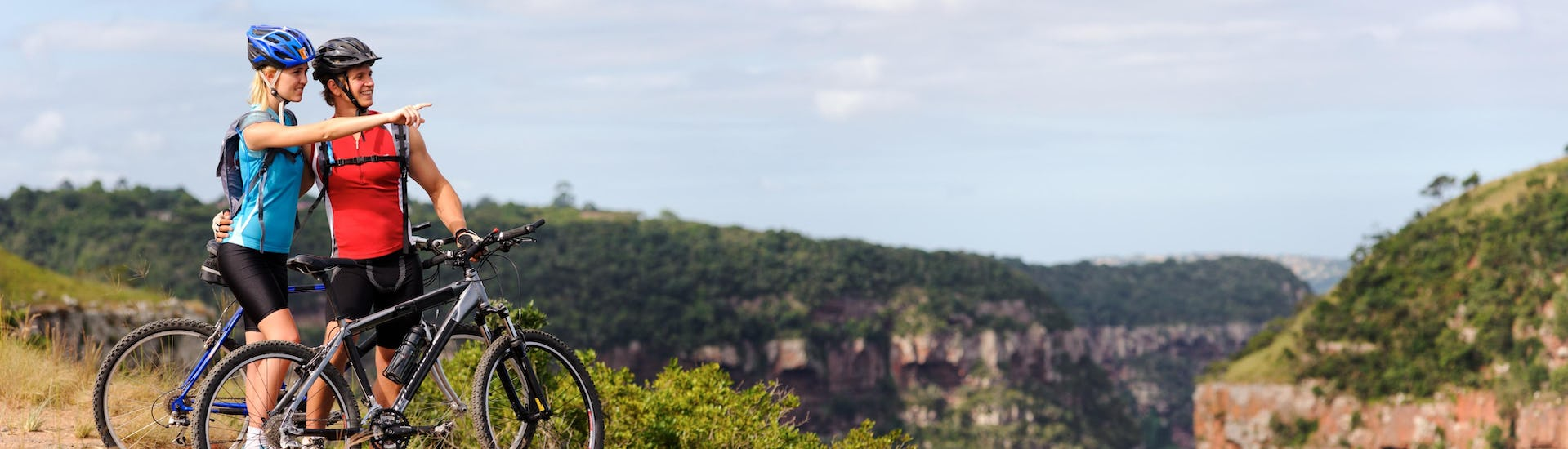 Couple is mountainbiking and enjoying the view during a stop