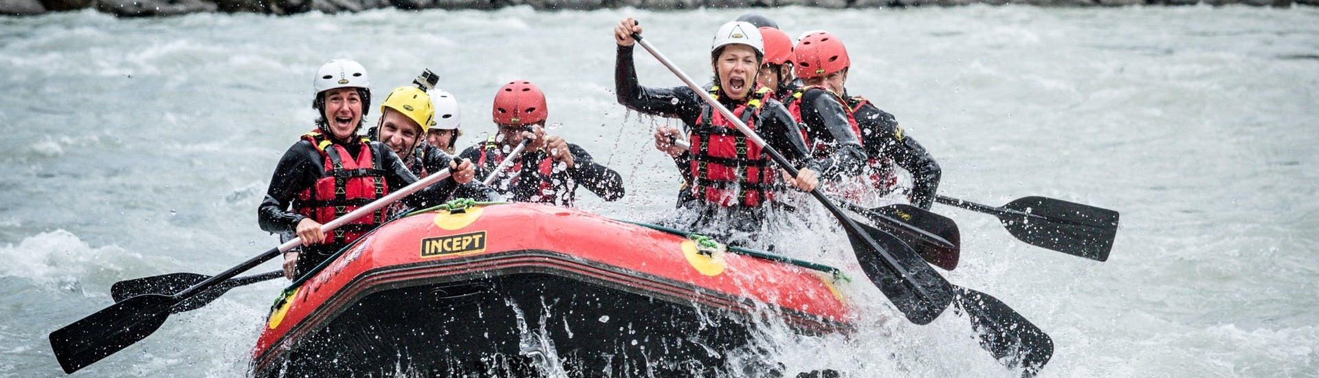 The participants of a rafting tour organized by Natur Pur Outdoorsports are facing splashing rapids in the Ötztal valley.