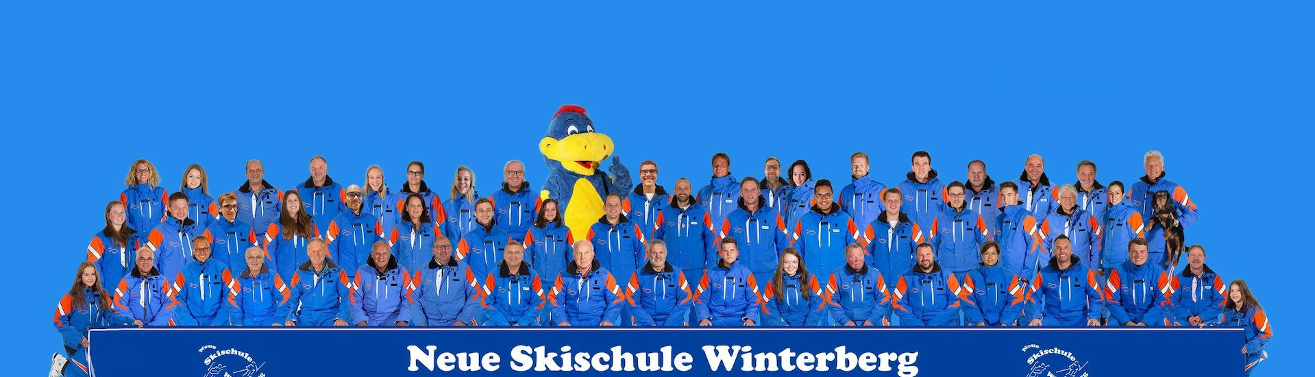 The ski instructors of the ski school Neue Skischule Winterberg are posing for a team photo with their mascot Oli.