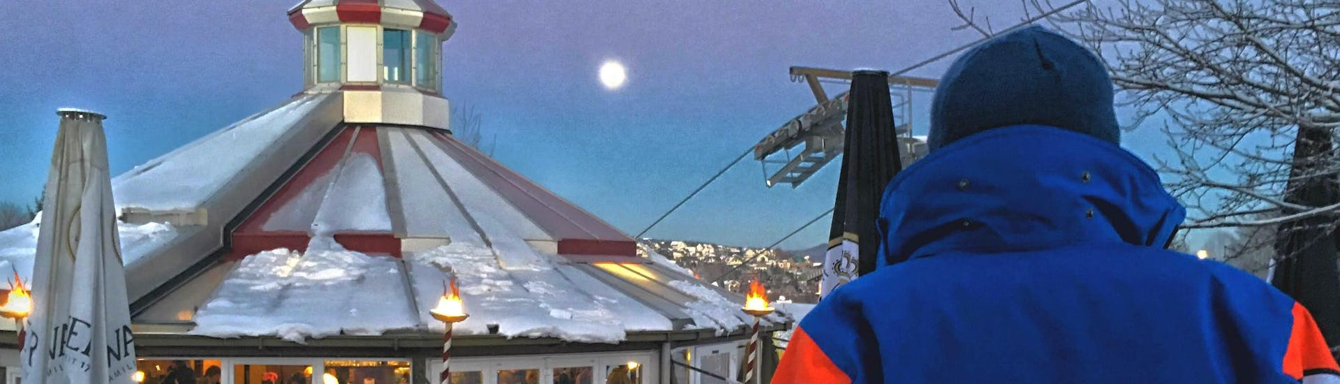A ski instructor of the ski school Neue Skischule Winterberg is enjoying the view of the moon during the Private Night Ski Lessons - All Levels in Winterberg.