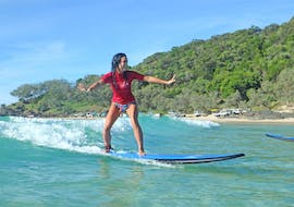 A young woman is all smiles as she rides her first waves during the Noosa surf lessons for beginners with Epic Ocean adventures Noosa.