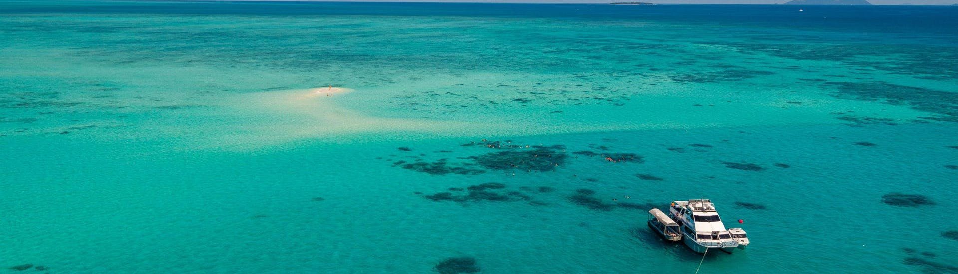 A luxury catamaran is moored in the shallow waters close to Upolu Reef Cay during a trip offered by Ocean Freedom Cairns.