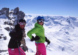 Two skiers are smiling in front of a glacier ready for their freeriding adventure during their Off-Piste Skiing Lessons with the ski school Evolution 2 Tignes.