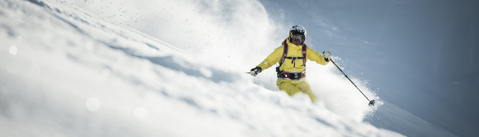 A skier is making his way down a deep powder snow slope during his off piste skiing lessons.