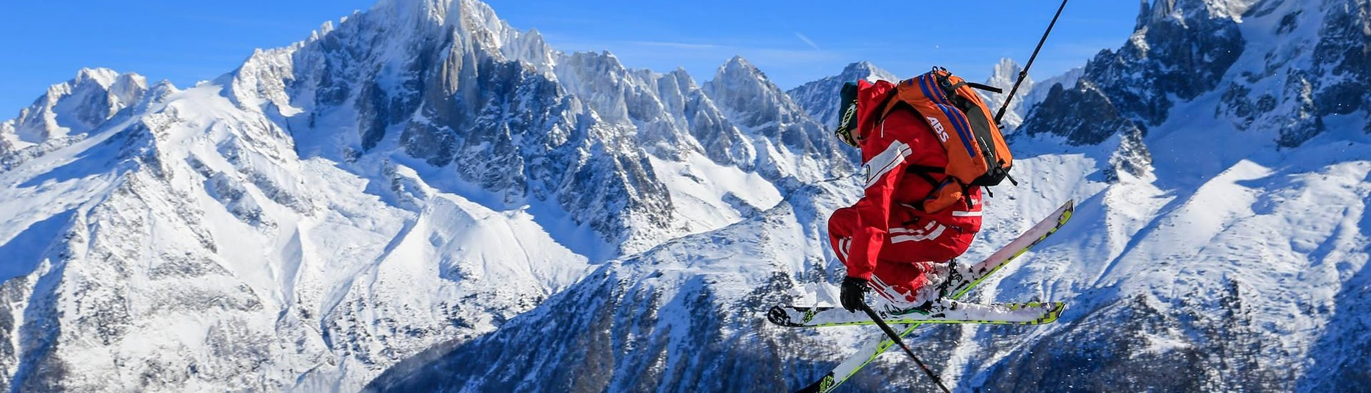 """In front of a mountain backdrop a skier is jumping while freeriding during his Off-Piste Skiing Tour """"Mont Blanc Ski Discovery"""" with the ski school ESF Chamonix."""