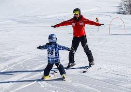Skilehrer fährt rückwärts die Piste und lernt Kleinkind den Schneepflug
