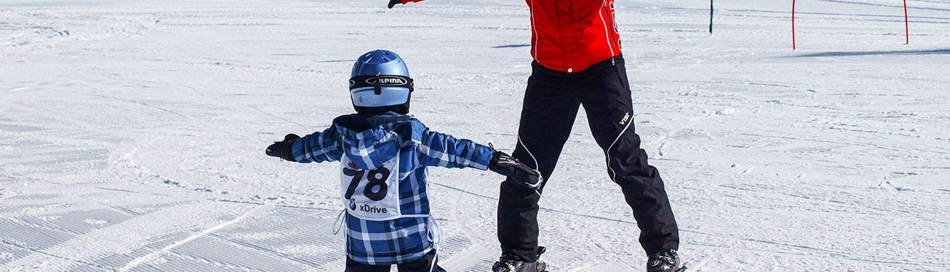 Skiinstructor skis backwards and teaches the little kid a snow plough