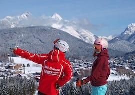 Skilehrer zeigt Skischülerin einen Berg in der Ferne